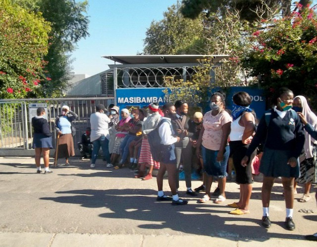 Photo of parents and learners outside a school