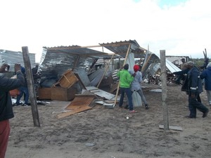 Photo of people next to destroyed shack