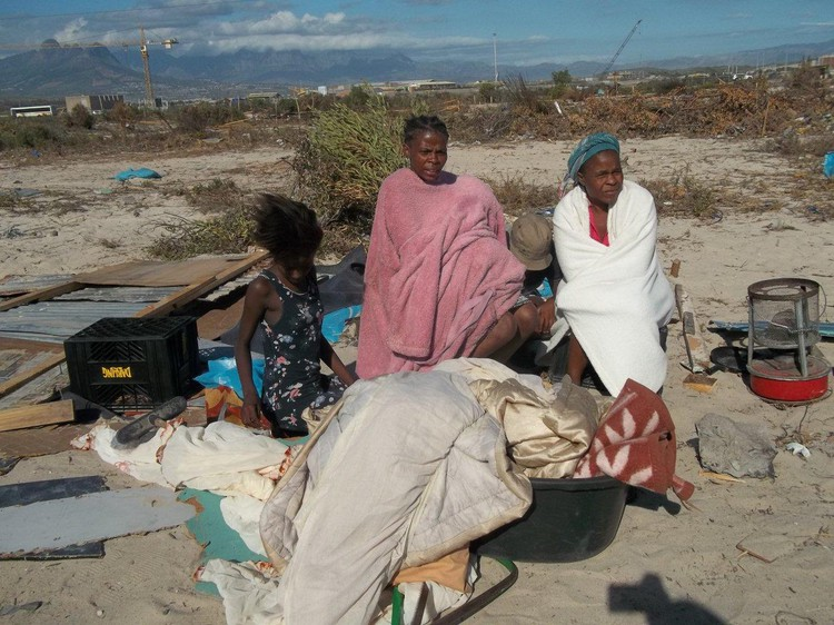 Photo of women sitting with their belongings on the ground after an eviction