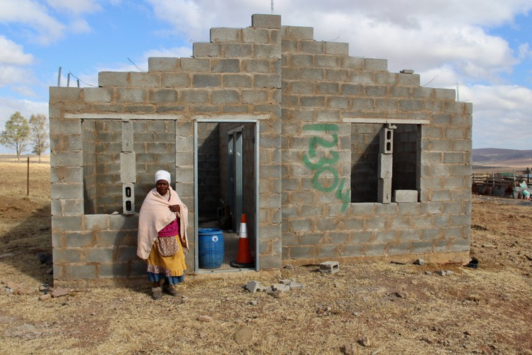 Photo of a woman in front of a half built house