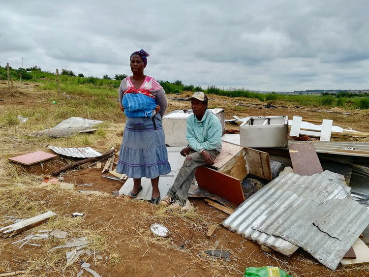 Photo of two people with a demolished shack