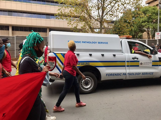 Wits students walk behind the Gauteng Pathology Services van as it removed the body of the bystander killed during student protests.