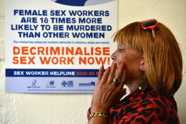 Photo of woman next to poster calling for decriminalisation of sex work