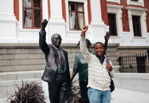 "Right2Know campaigner Sizwe Manqele shouts ""Amandla!"" outside parliament on Wednesday. Photo by Shadi Garman."