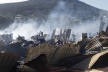 Smoke rises from the ruins of shacks in Imizamo Yethu Hout Bay.