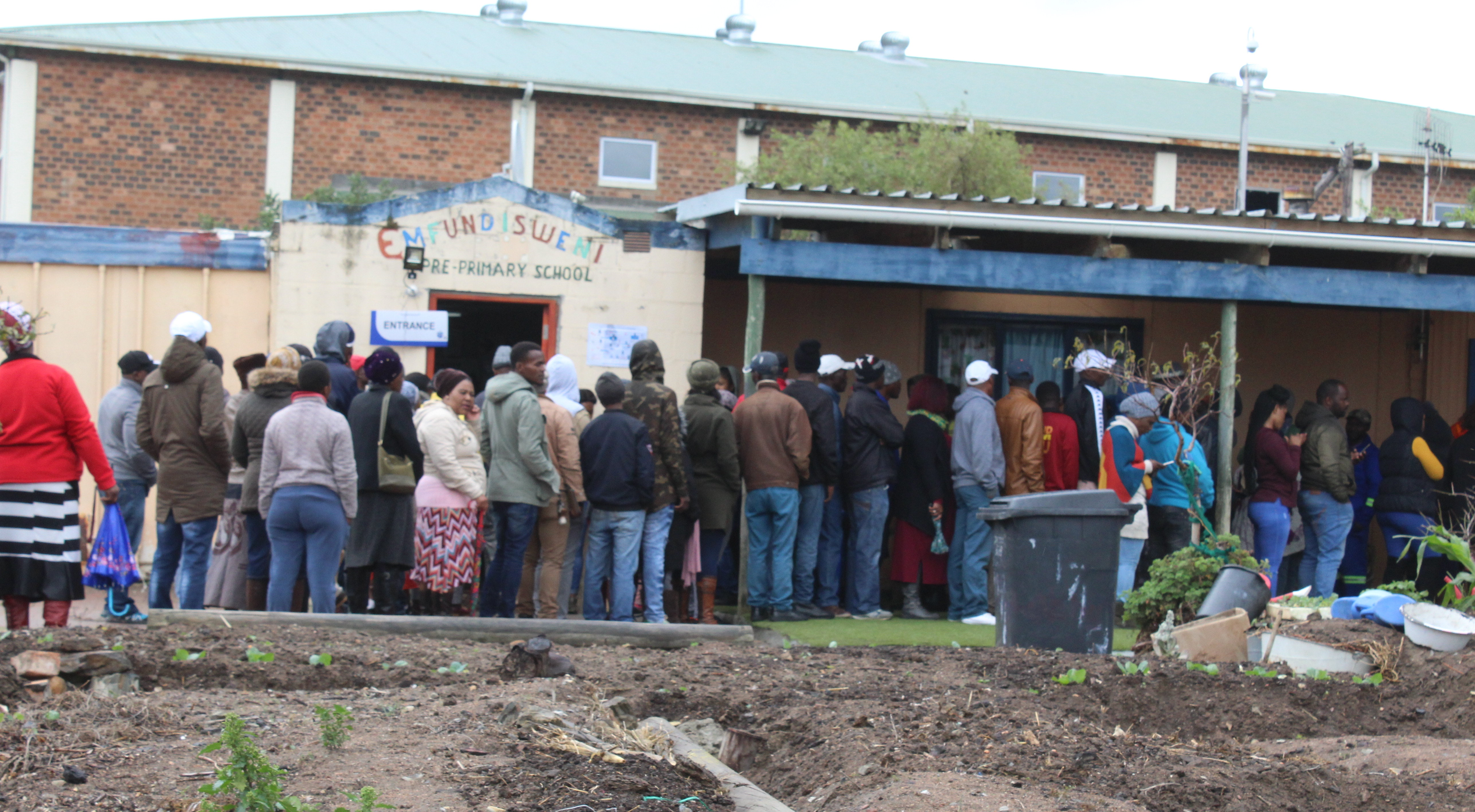 Photo of people standing queue to vote