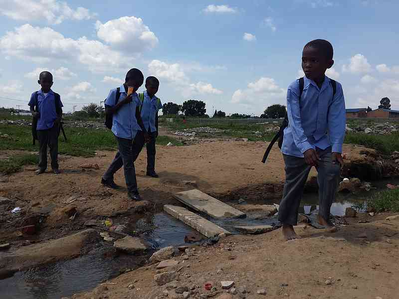 Photo of school children crossing river