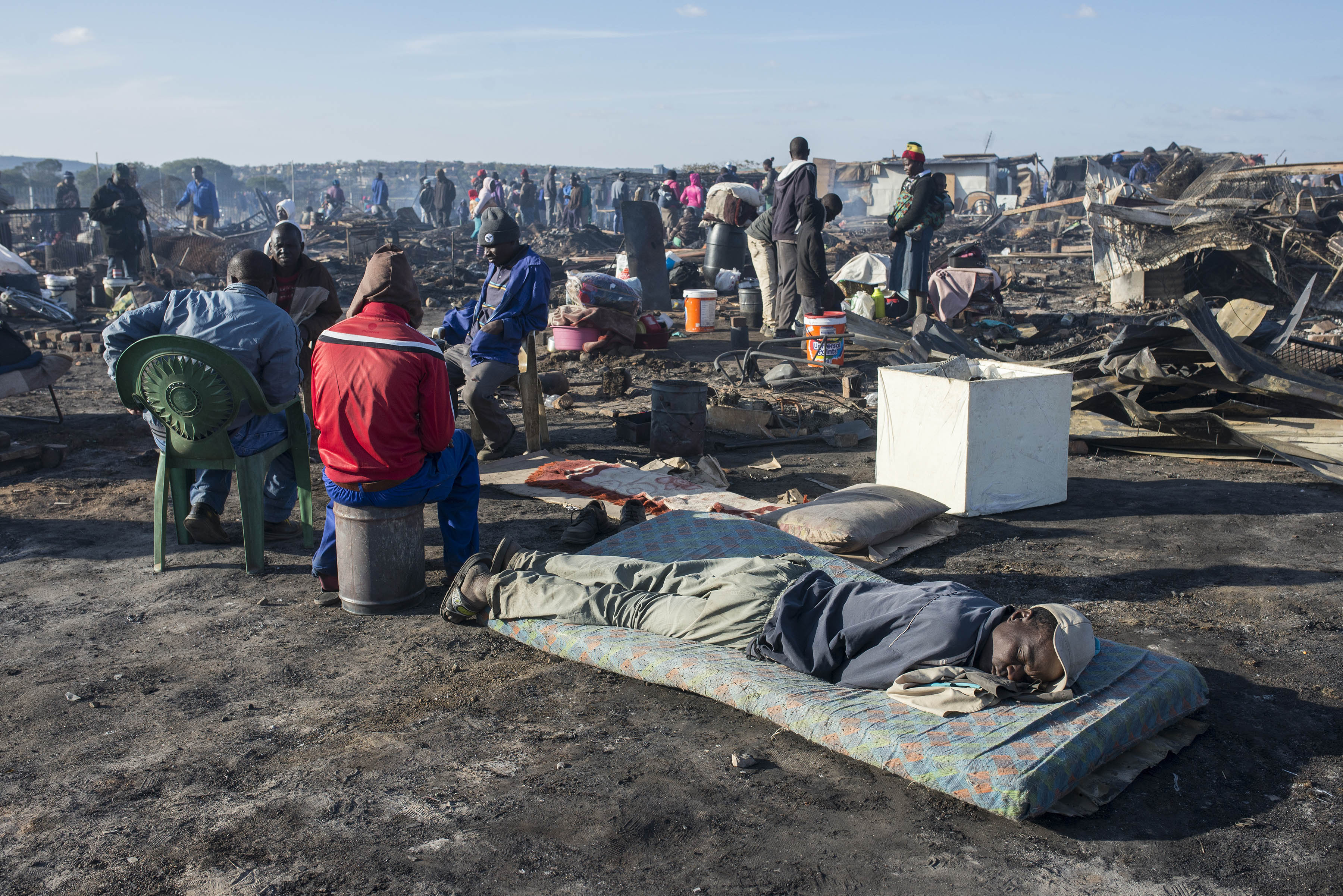 Photo of people in burnt out settlement